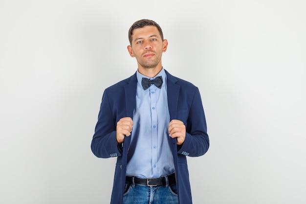 Молодой человек держит куртку в костюме, джинсах и выглядит серьезно