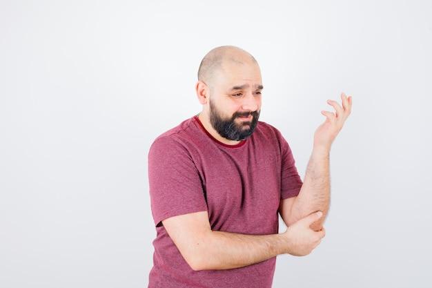 Молодой человек, держащий левую руку на локте, думает о чем-то в розовой футболке и задумчиво смотрит, вид спереди.