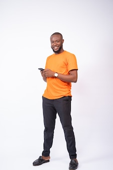 Young man holding his phone smiling, standing on a white background, texting concept