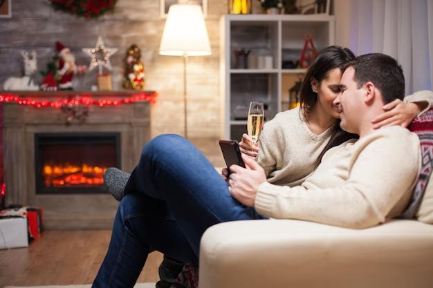 ソファに座ってクリスマスの日に彼の妻に愛情を示しながら彼のスマートフォンを保持している若い男。
