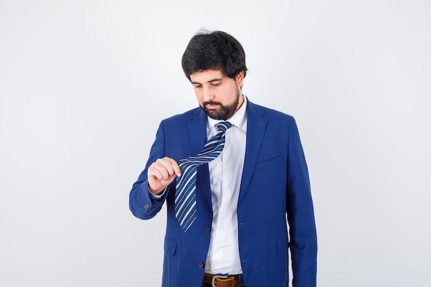 Giovane che tiene la cravatta in camicia, giacca, cravatta e sembra concentrato, vista frontale.