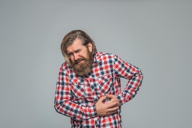 그의 배를 들고 젊은 남자 수염 난 남자는 고통을 느낀다 복통 문제 질병 초상화 개념