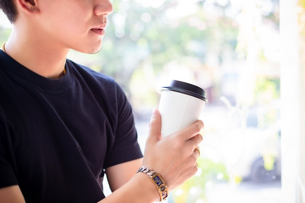 Young man holding hot coffee