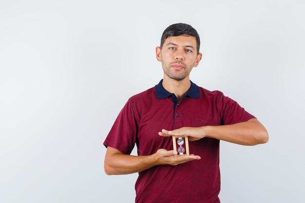 Tシャツに砂時計を持って、賢明な正面図を探している若い男。