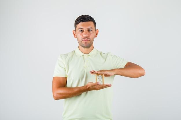 Tシャツに砂時計を保持している若い男