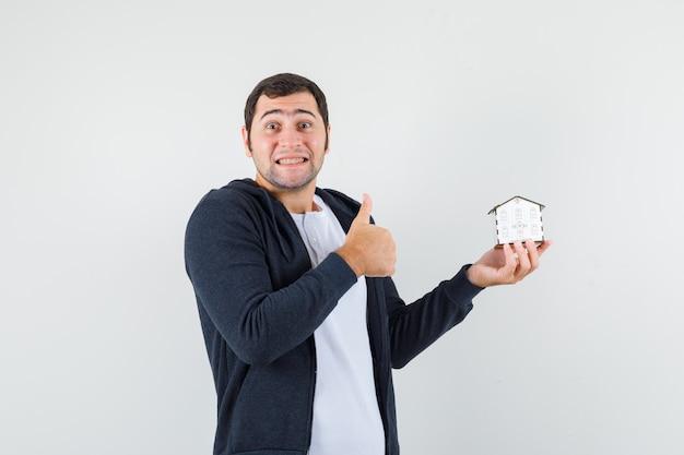 家のモデルを保持し、白いtシャツとジップフロントの黒いパーカーで親指を見せて楽観的に見える若い男。正面図。