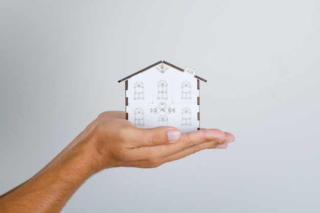 Young man holding house model in his hands.