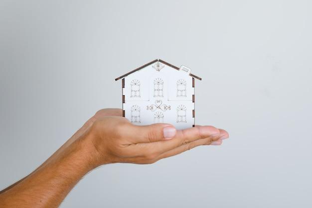 若い男が彼の手で家のモデルを保持しています。