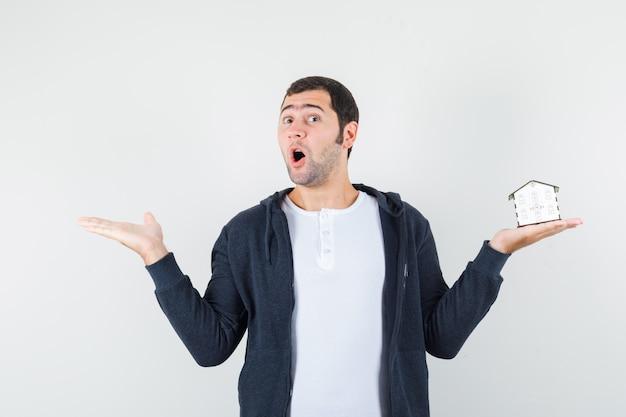 片手に家のモデルを持ち、もう片方の手を白いtシャツとジップフロントの黒いパーカーで左に伸ばして驚いた正面図を見る若い男。