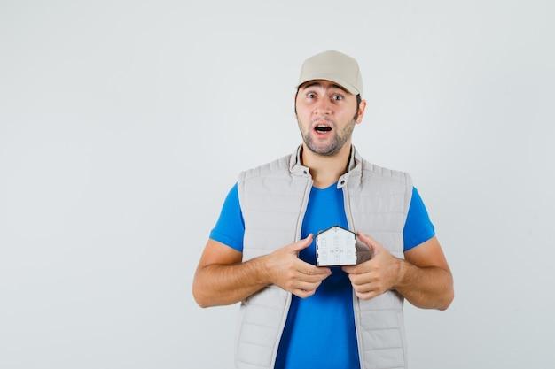 Tシャツ、ジャケット、キャップで家のモデルを保持し、驚いて見える、正面図の若い男。