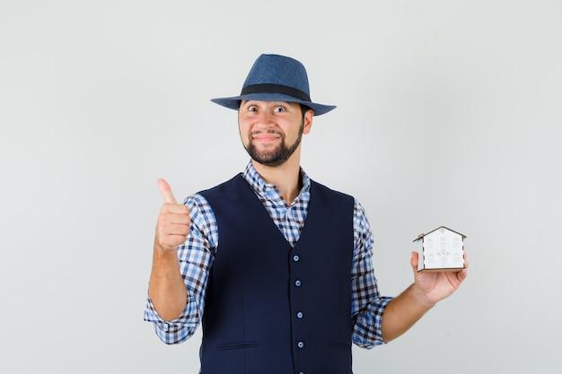 家のモデルを保持している若い男、シャツ、ベスト、帽子で親指を表示し、陽気に見える、正面図。
