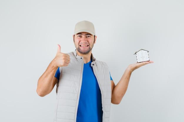 家のモデルを保持し、tシャツ、ジャケット、キャップで親指を表示し、うれしそうに見える若い男。正面図。