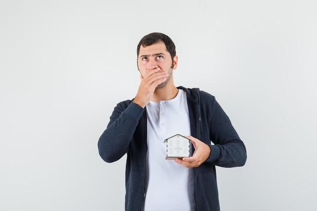 Молодой человек держит модель дома, думает о чем-то в белой футболке и черной толстовке с капюшоном на молнии и выглядит задумчиво. передний план.