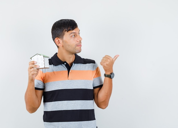 Young man holding house model while pointing away in t-shirt and looking curious