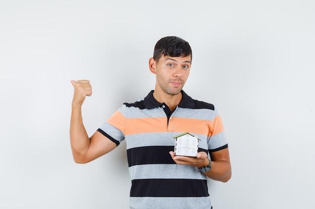 Молодой человек держит модель дома, указывая назад в футболке и выглядит веселым