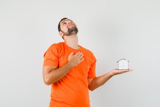 Giovane che tiene il modello della casa con la mano sul petto in maglietta arancione e sembra sognante. vista frontale.