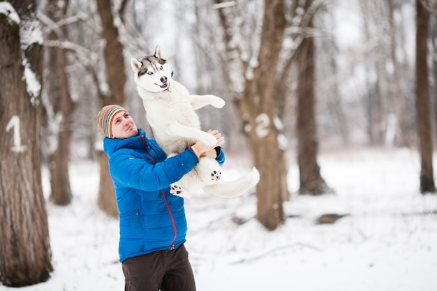 Young man holding a husky puppy in the winter forest. horizontal outdoors shot.