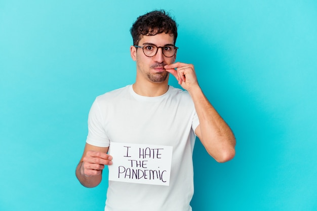 Young man holding a i hate the pandemic placard isolated with fingers on lips keeping a secret