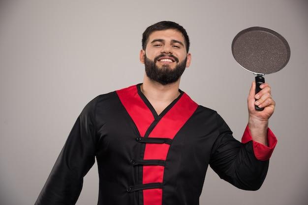 Молодой человек держит в руке темную сковороду.