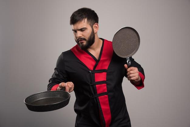 Молодой человек держит в руках две темные сковороды.