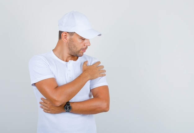Young man holding and looking at arm in white t-shirt, cap, front view.