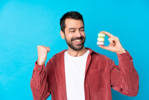 Young man holding macaroons over isolated wall