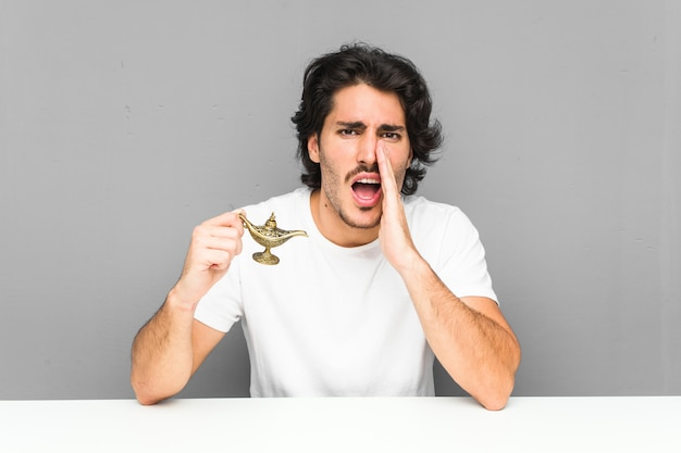 Young man holding a magic lamp shouting excited to front