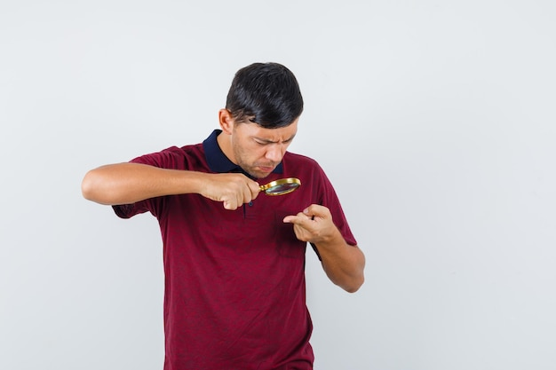 Young man holding magnifying glass over finger in t-shirt and looking careful. front view.