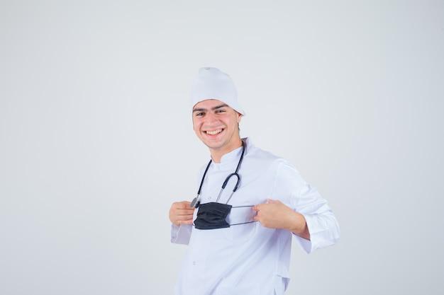 Giovane che tiene la maschera mentre sorride in uniforme bianca e sembra allegro. vista frontale.
