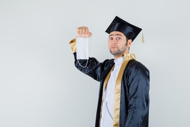Giovane che tiene mascherina medica in uniforme laureato e guardando perplesso, vista frontale.