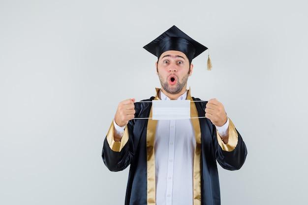Молодой человек держит медицинскую маску в униформе выпускника и смотрит удивленно, вид спереди.