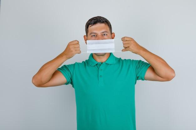 若い男が緑のtシャツの口の上に医療用マスクを押し、注意深く、正面を探しています。