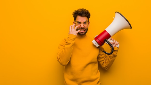 Young man holding a megaphone angry and upset