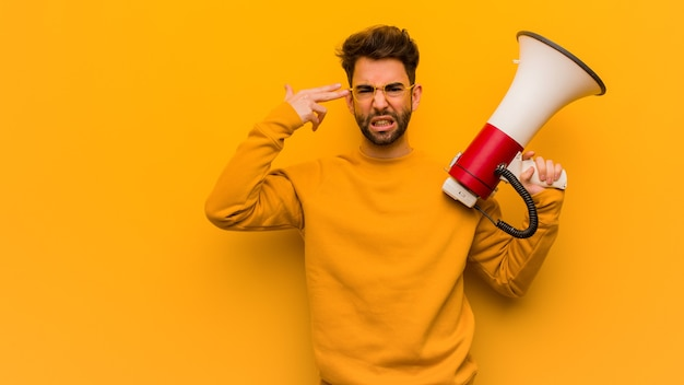 Young man holding a megaphone doing a suicide gesture