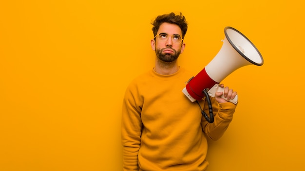 Young man holding a megaphone tired and bored