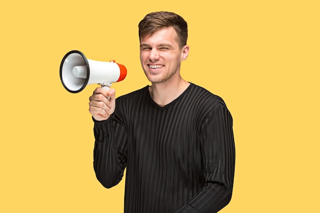 The young man holding a megaphone on on yellow background