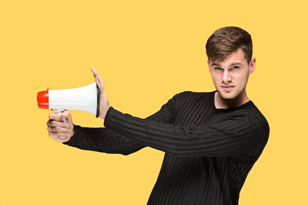 Young man holding a megaphone on on yellow studio background