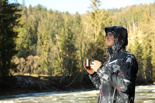 森の中で飲み物と金属カップを保持している若い男