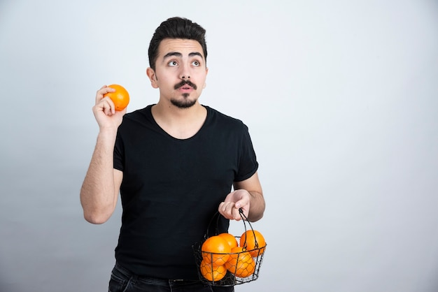 Young man holding metallic basket full of orange fruits .