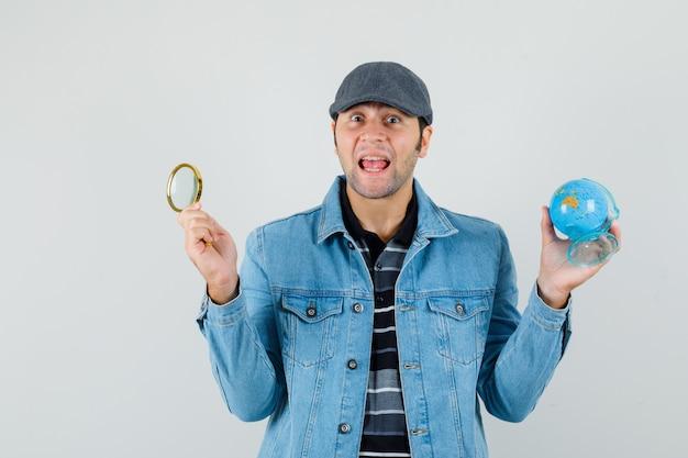 미니 글로브, 재킷, 모자에 돋보기를 들고 놀 찾고 젊은 남자.