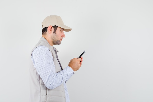 Молодой человек держит мобильный телефон под рукой в бежевой куртке и кепке и выглядит серьезно. передний план.