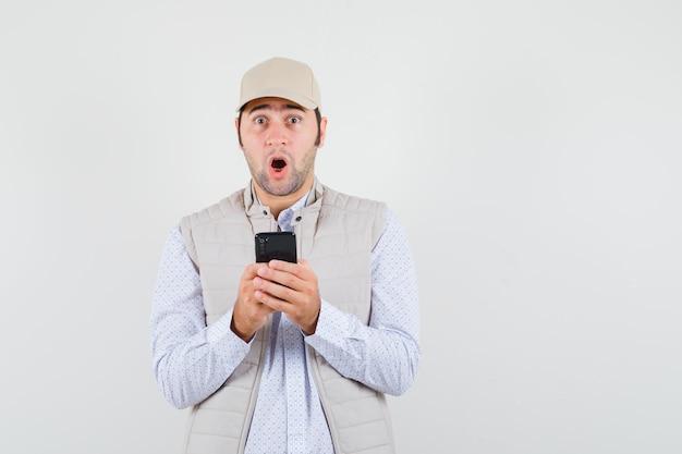 베이지 색 재킷과 모자에 손에 휴대 전화를 들고 놀 찾고 젊은 남자. 전면보기.