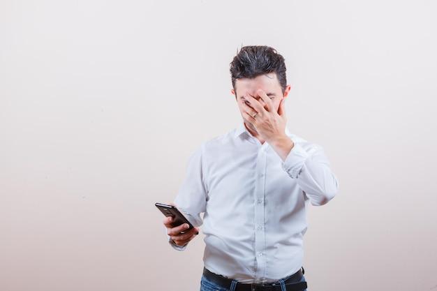 Giovane che tiene il telefono cellulare, copre il viso con la mano in camicia, jeans e sembra ansioso