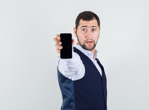 Молодой человек держит мобильный телефон в рубашке и жилете