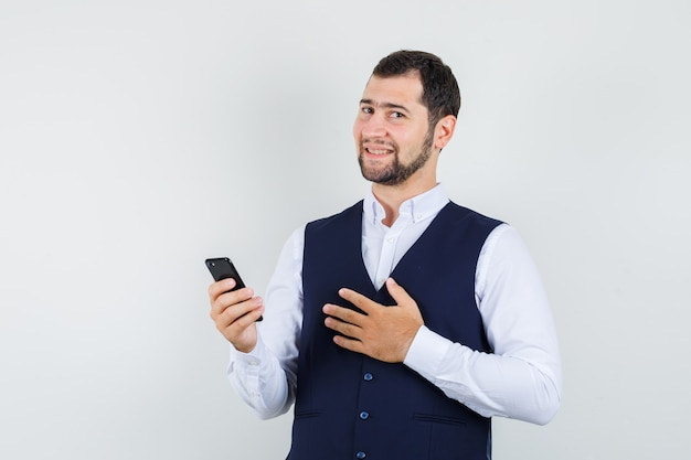 シャツ、ベスト、陽気に見える携帯電話を保持している若い男