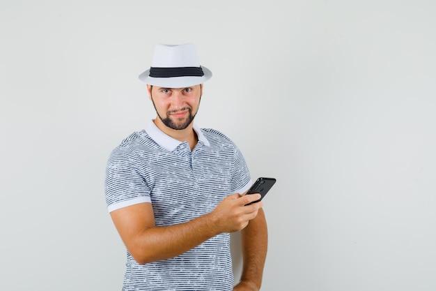 티셔츠, 모자에 휴대 전화를 들고 교활한 찾고 젊은 남자. 전면보기.