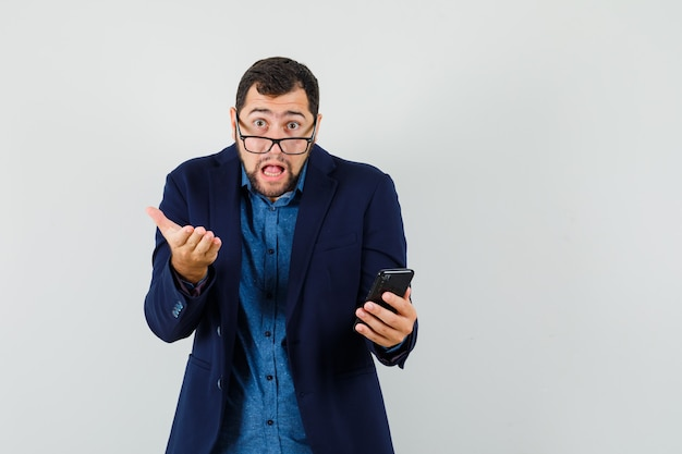 Young man holding mobile phone in shirt, jacket and looking shocked