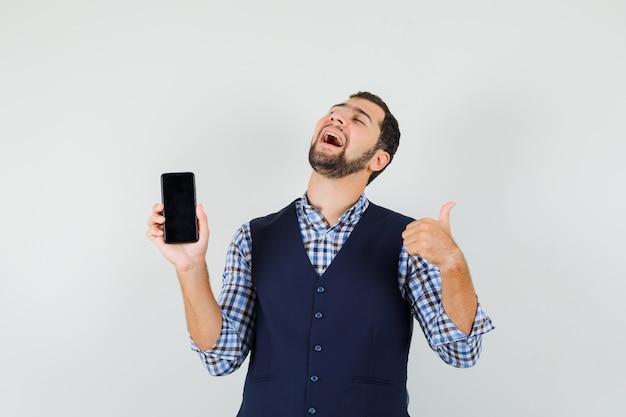 携帯電話を持っている若い男、シャツに親指を表示