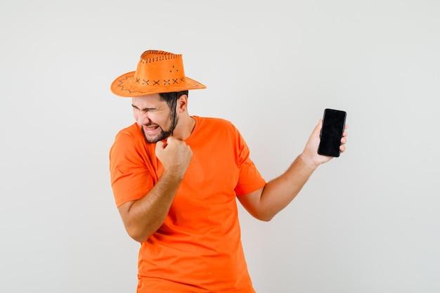 Молодой человек держит мобильный телефон с жестом победителя в оранжевой футболке, шляпе и выглядит счастливым, вид спереди.