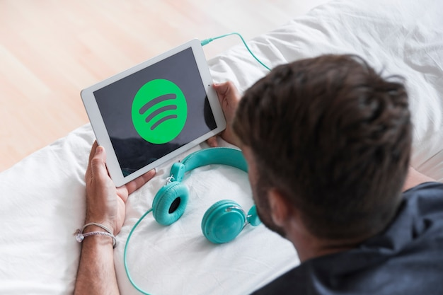Young man holding modern device with spotify app